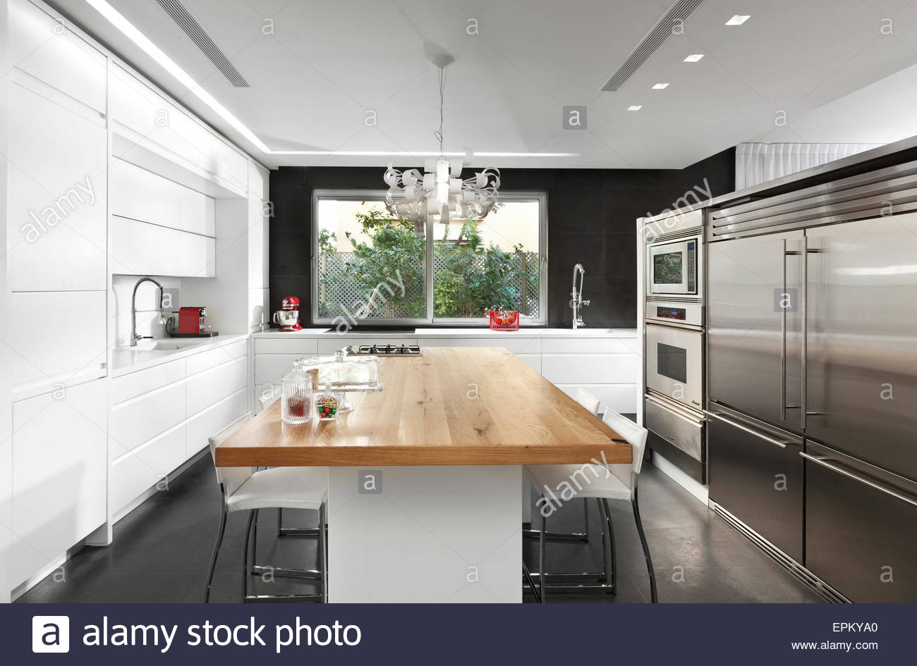 Black And White Kitchen With Wooden Dining Table In Modern Villa Givat Smuel Israel