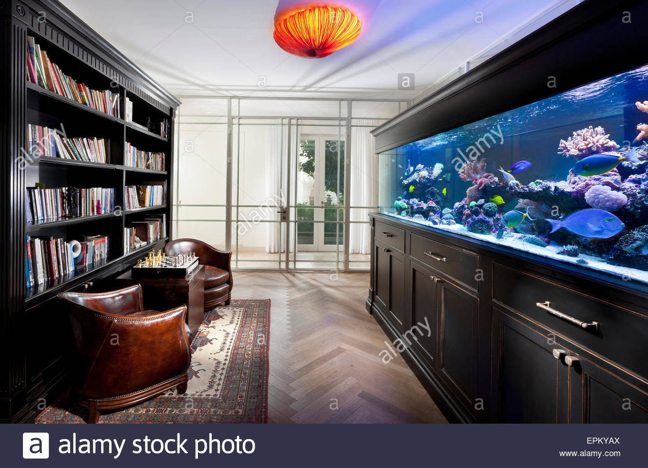 Room with large fish tank and bookcase leather armchairs for Bookshelf fish tank