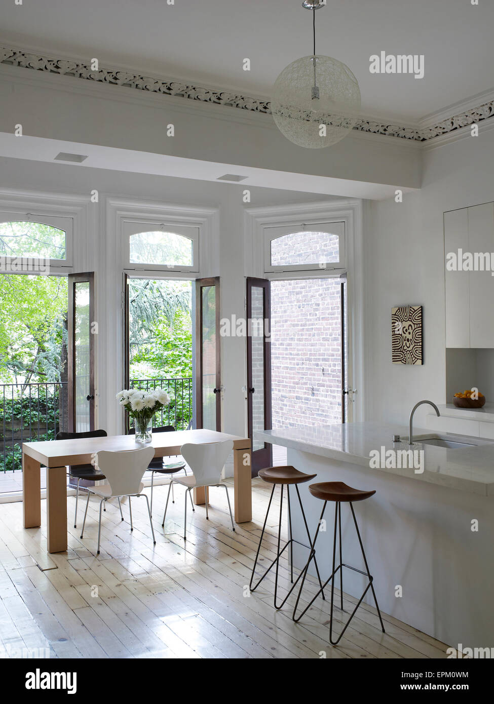 Breakfast Bar, Stools And Small Dining Table In White Kitchen With Open  Glass Doors Leading To Garden, Chelsea Townhouse, New York, USA
