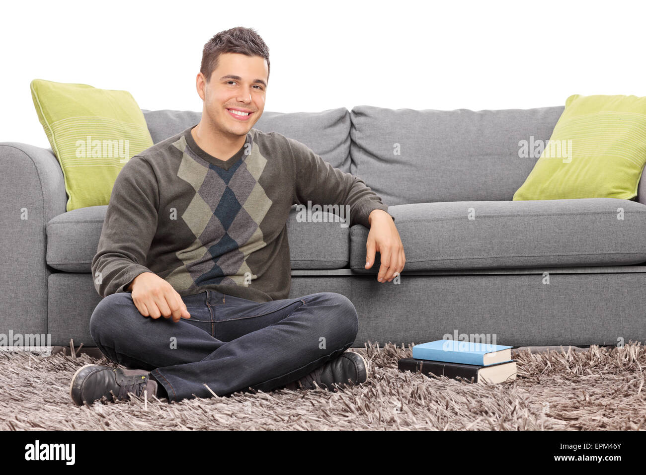 Relaxed young guy sitting on the floor in front of a gray sofa ...