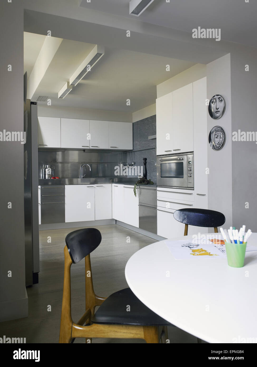 interior of modern kitchen with a table and chairs in front two fornasetti plates hanged