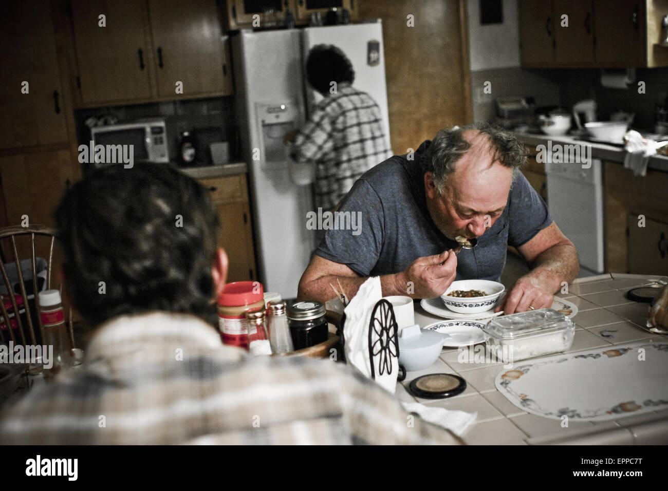 a father and son eat dinner at the kitchen table after milking the EPPC7T
