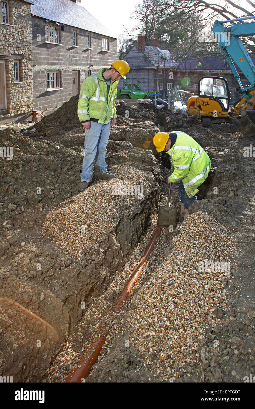 Construction Workers Install Plastic Underground Drainage