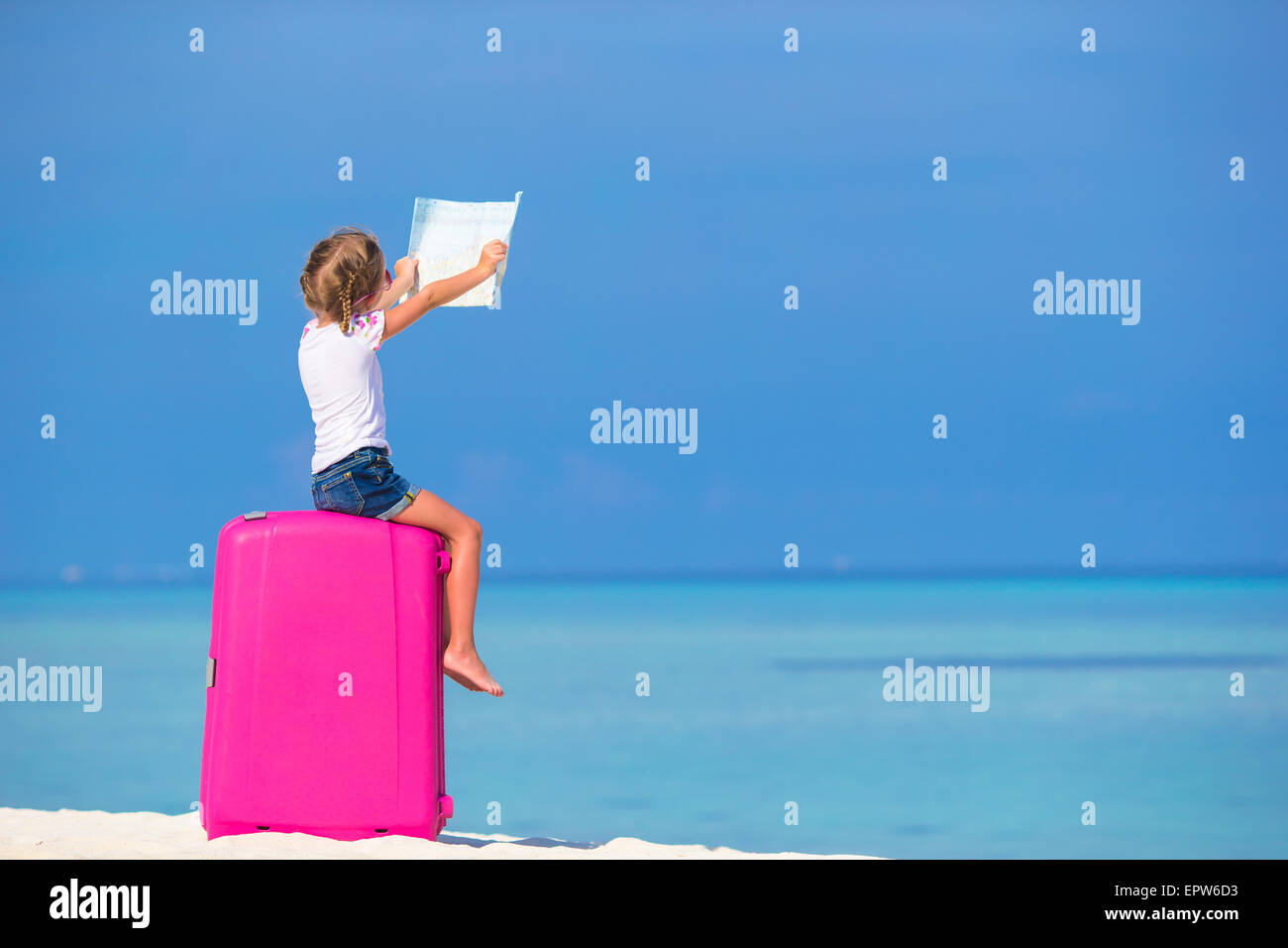 Little adorable girl with big pink suitcase and map of island on ...