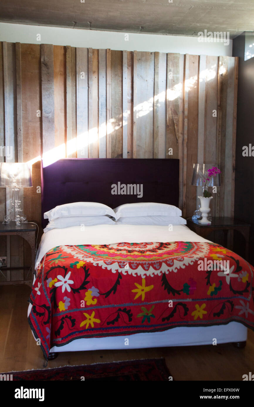 bed with dark purple headboard and mexican inspired throw with  - bed with dark purple headboard and mexican inspired throw with woodpanelled wall in south african home