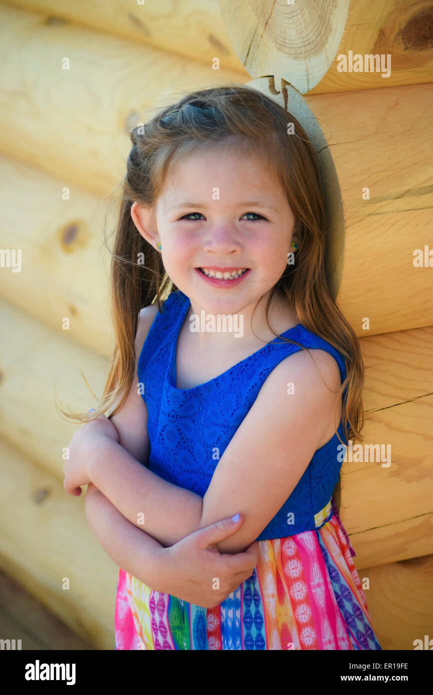Pretty 4 year old girl in colorful blue dress on log cabin for The girl in the cabin