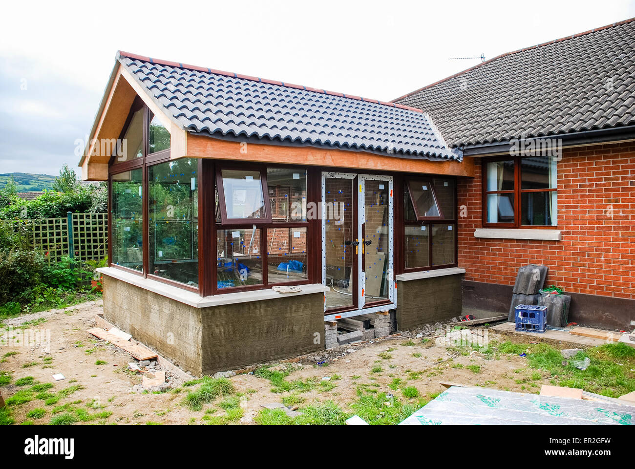 Sunroom extension being built onto a bungalow stock photo for Adding onto a manufactured home