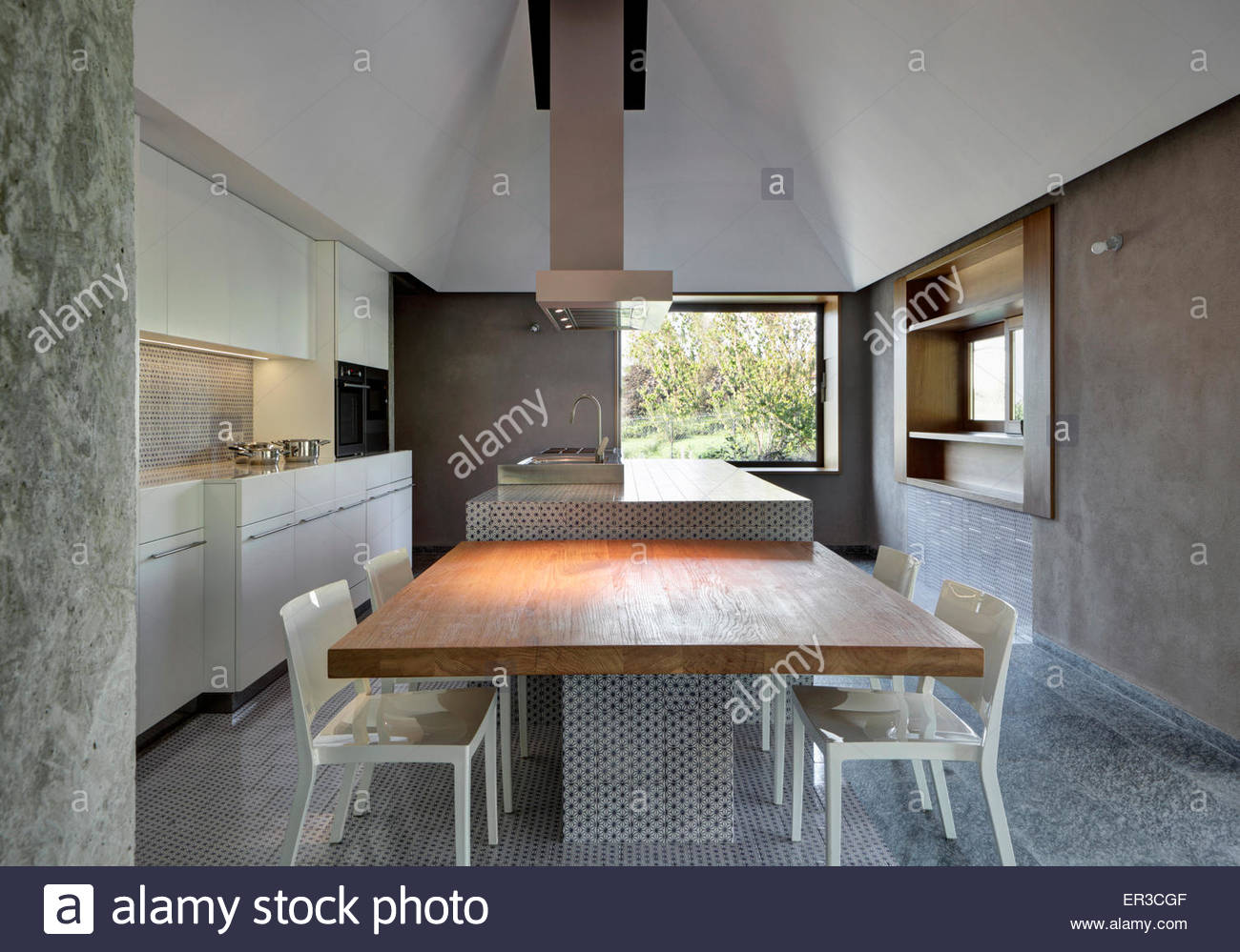Kitchen Table And Chairs With Island Unit And Extractor In Modern Italian Home