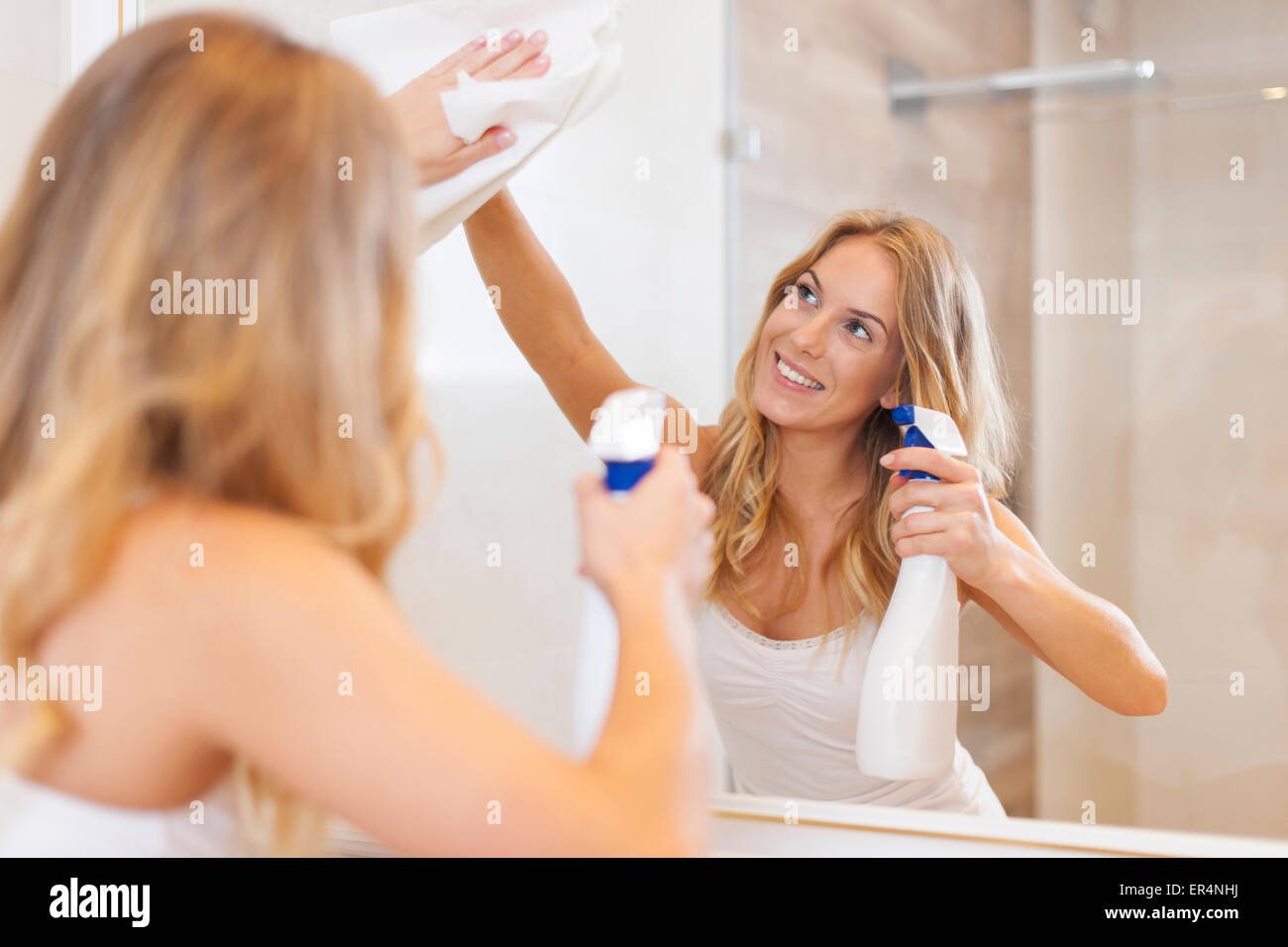 How to clean bathroom mirror - Young Blonde Woman Cleaning Mirror In Bathroom Debica Poland Stock Image