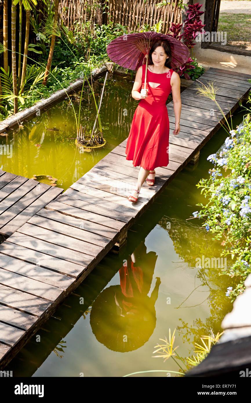 Beautiful Woman In Red Dress Walking Through A Thai Garden