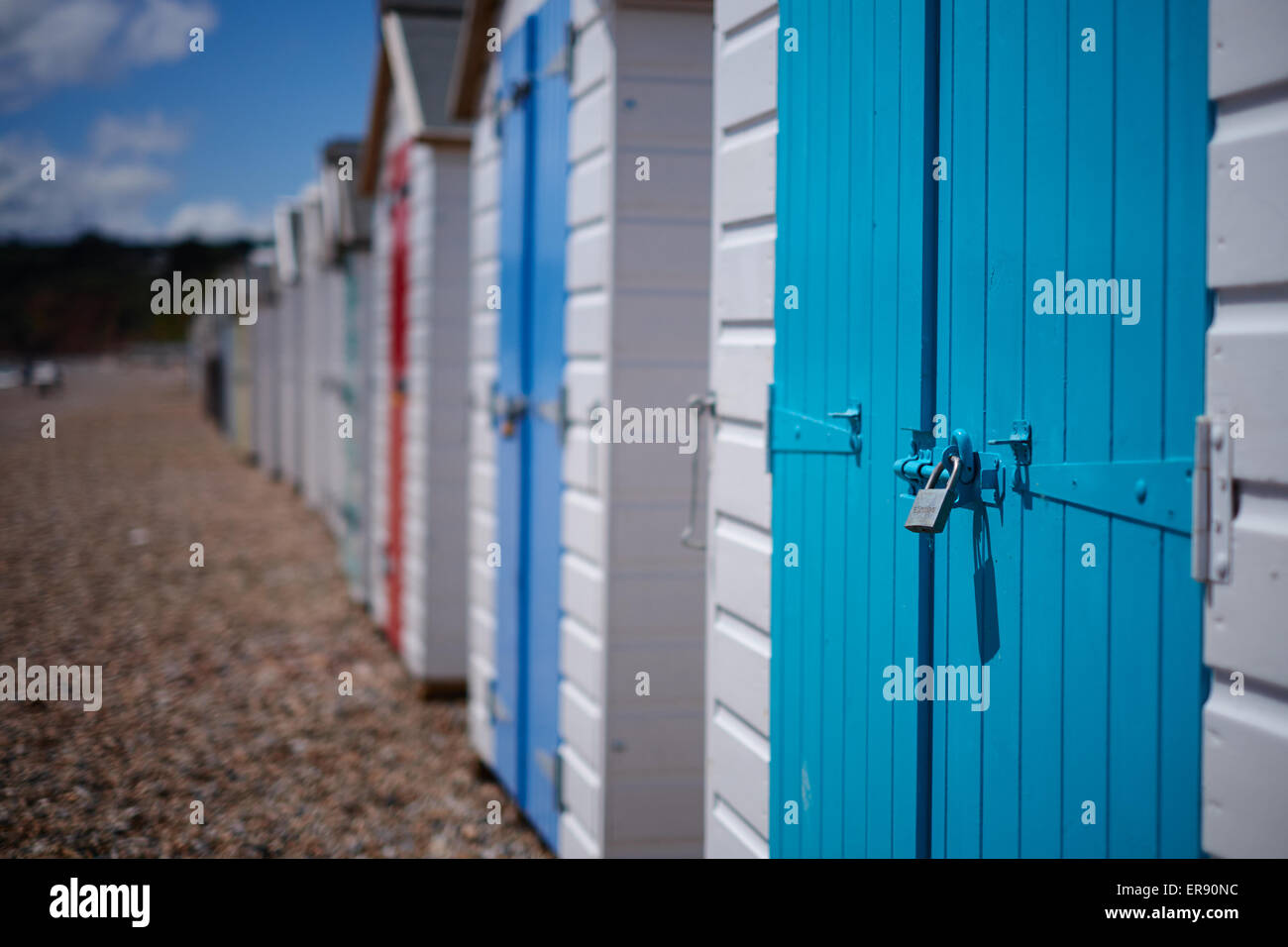 A row of beach huts with colourful doors on the pebble beach Devon UK & A row of beach huts with colourful doors on the pebble beach ...