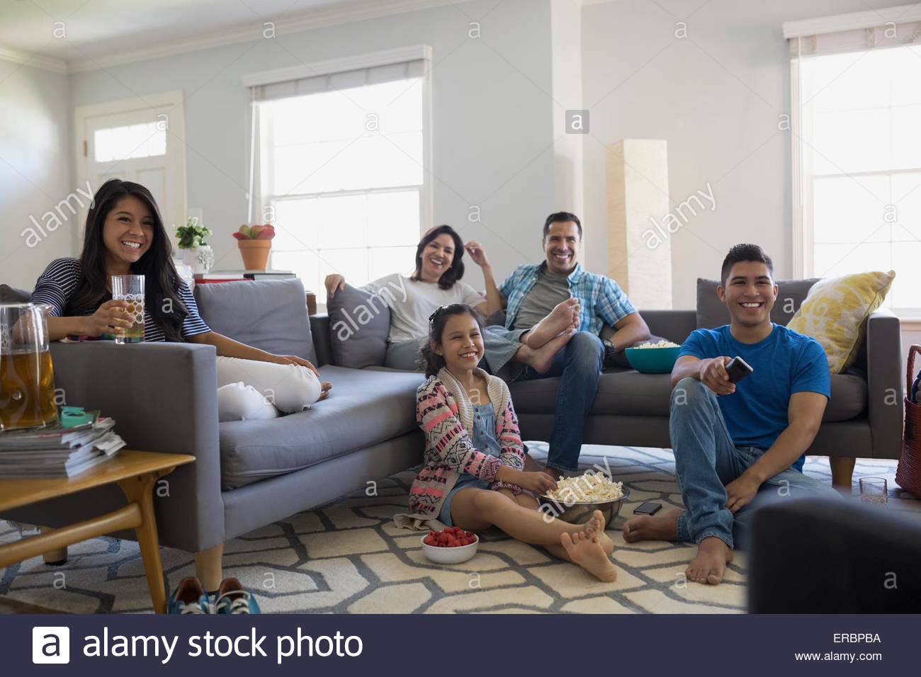 Family watching TV with popcorn in living room Stock Photo ...