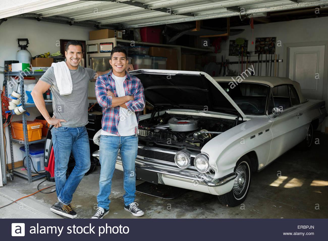 Portrait Father And Son Restoring Vintage Car Garage Stock