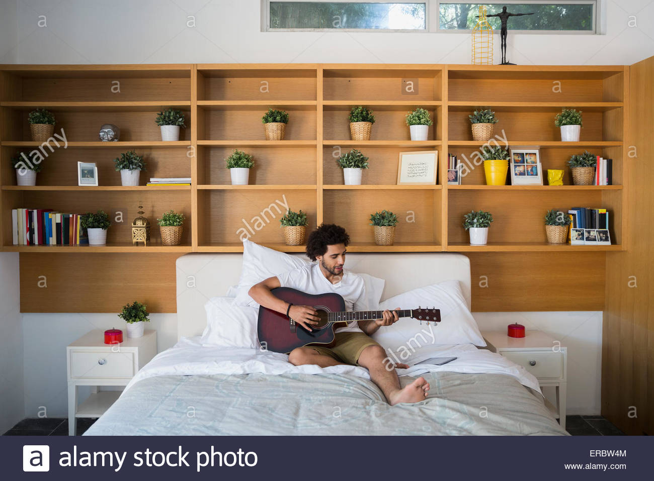 Man playing guitar on bed in bedroom   Stock Image. Acoustic Guitar Bedroom Stock Photos   Acoustic Guitar Bedroom