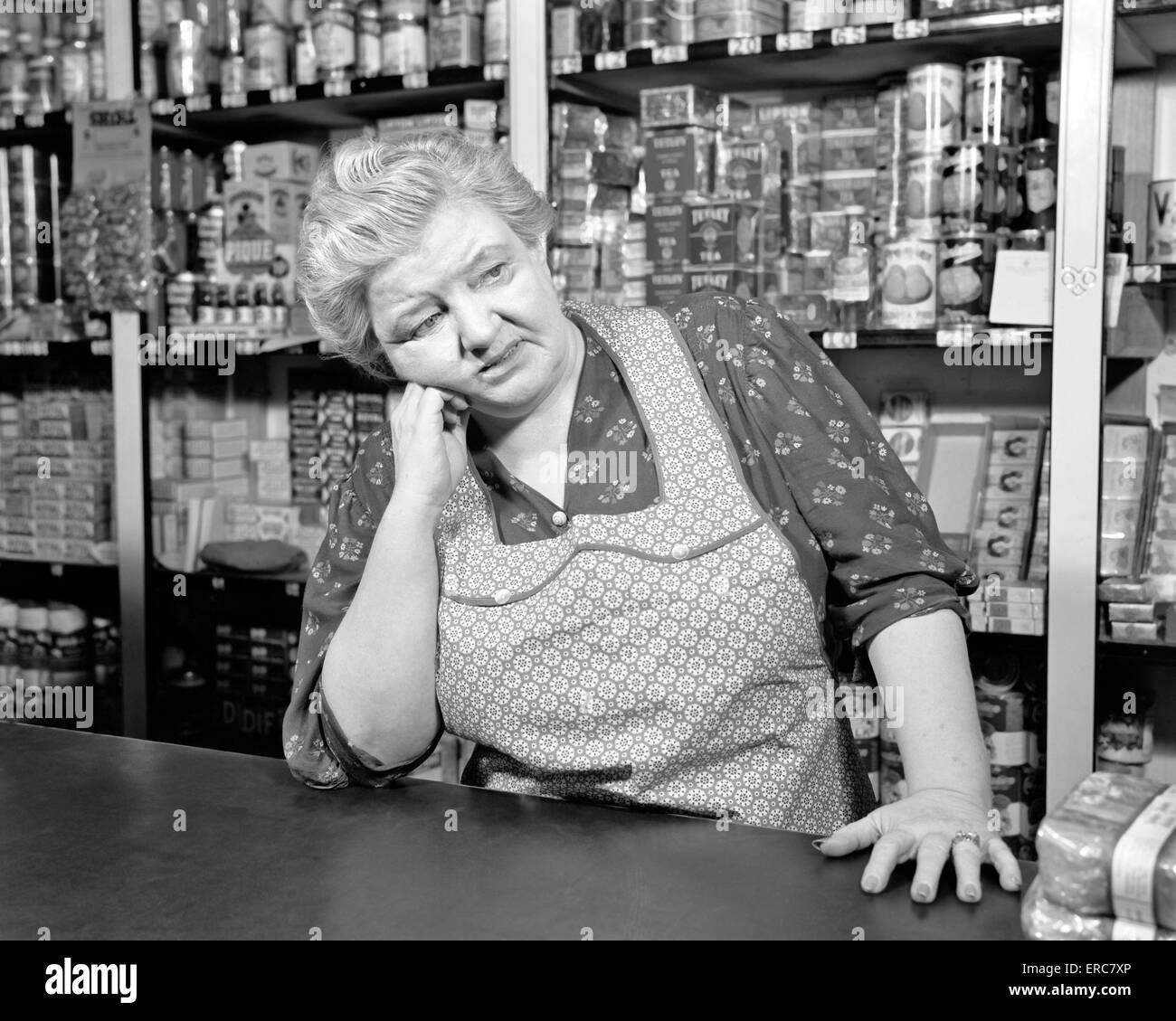 White apron in store -  1930s 1940s Sad Senior Woman Clerk Grocery Store Wearing Apron Canned Goods On Shelves Leaning Counter