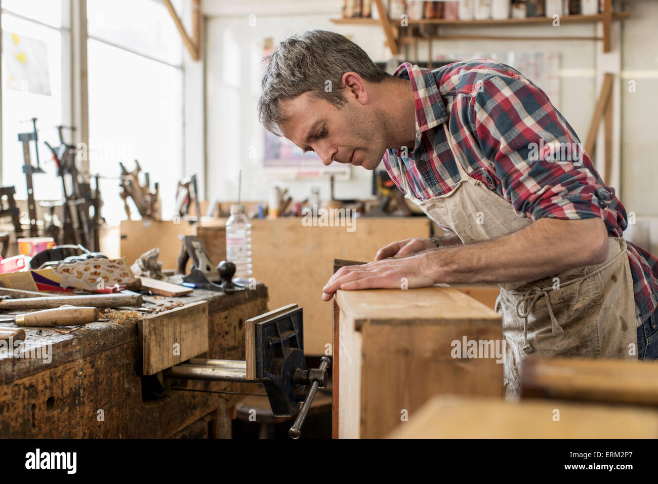 Perfect An Antique Furniture Restorer In His Workshop Using A Hand Tool To Smooth A  Wooden Object.