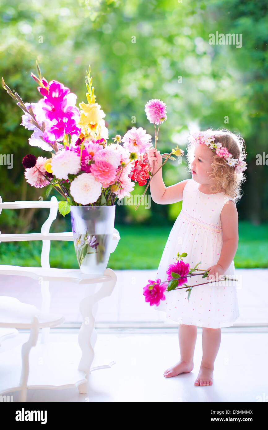 Little girl arranging flowers at home in a vase child playing little girl arranging flowers at home in a vase child playing indoors kids birthday reviewsmspy