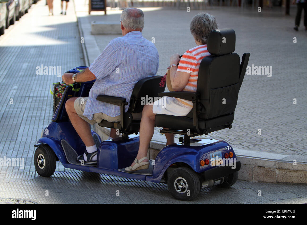 Elderly couple on mobility scooter tandem stock photo for Motorized cart for seniors