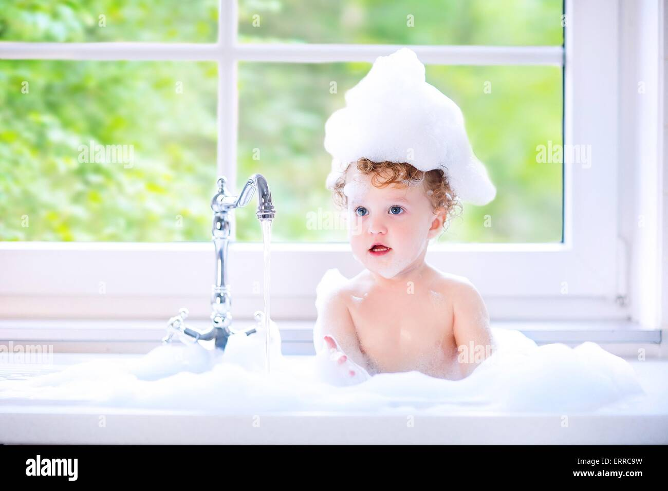 funny little baby girl with wet curly hair taking bath in a