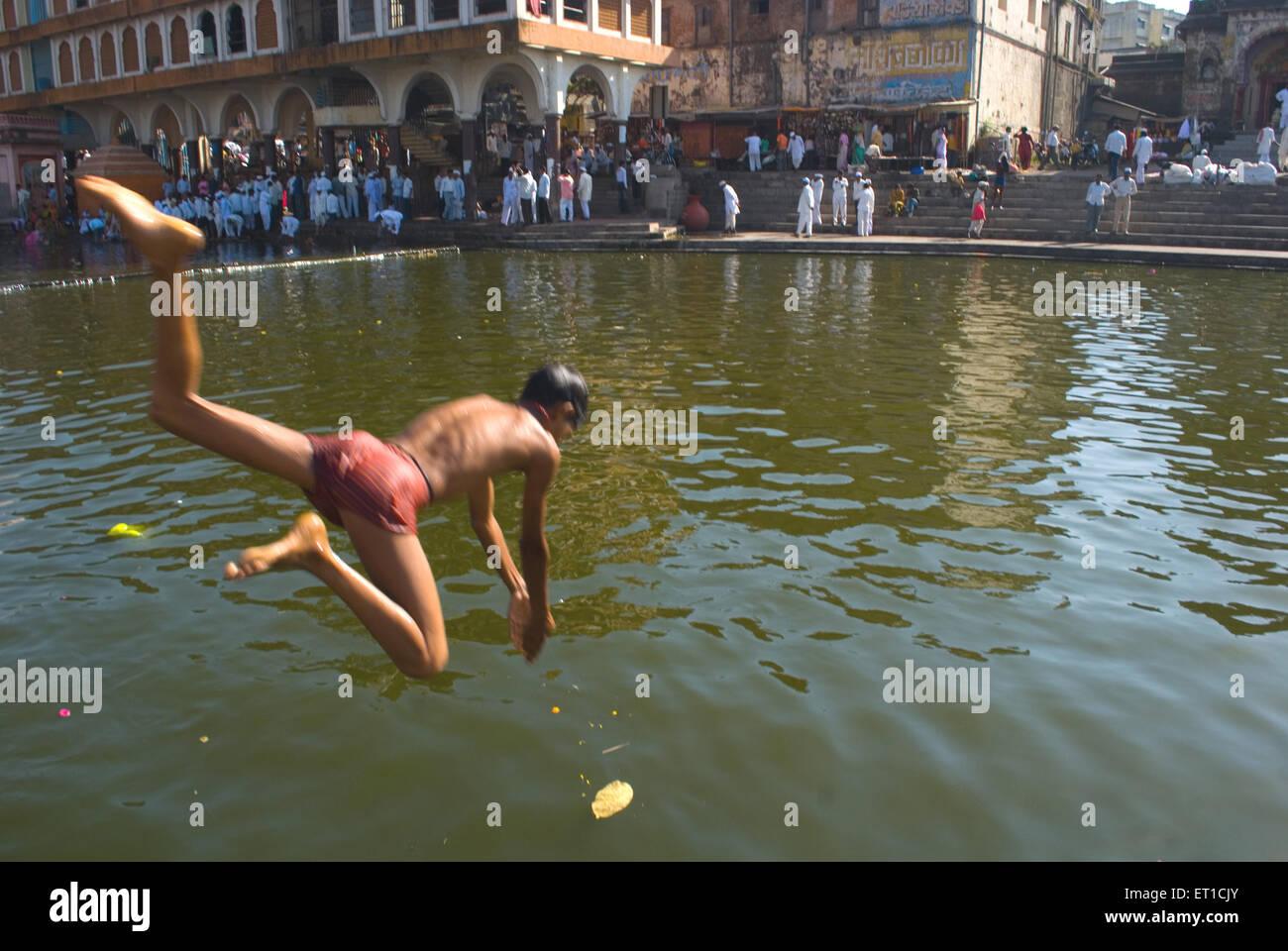 naked boy in river Boy diving in godavari river ; Ramghat ; Nasik ; Maharashtra ; India MR#704