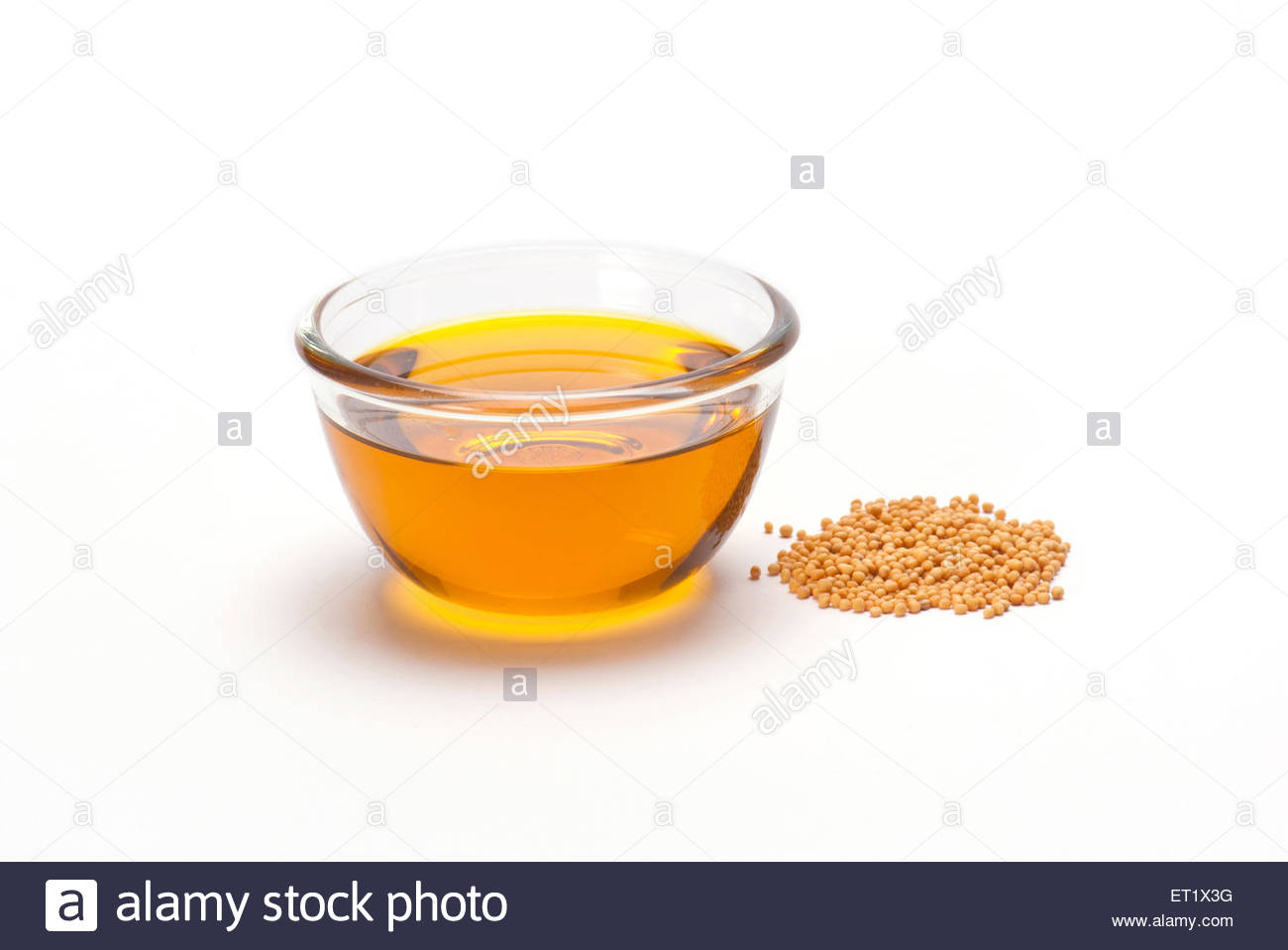 oil in bowl and mustard seeds on white background india