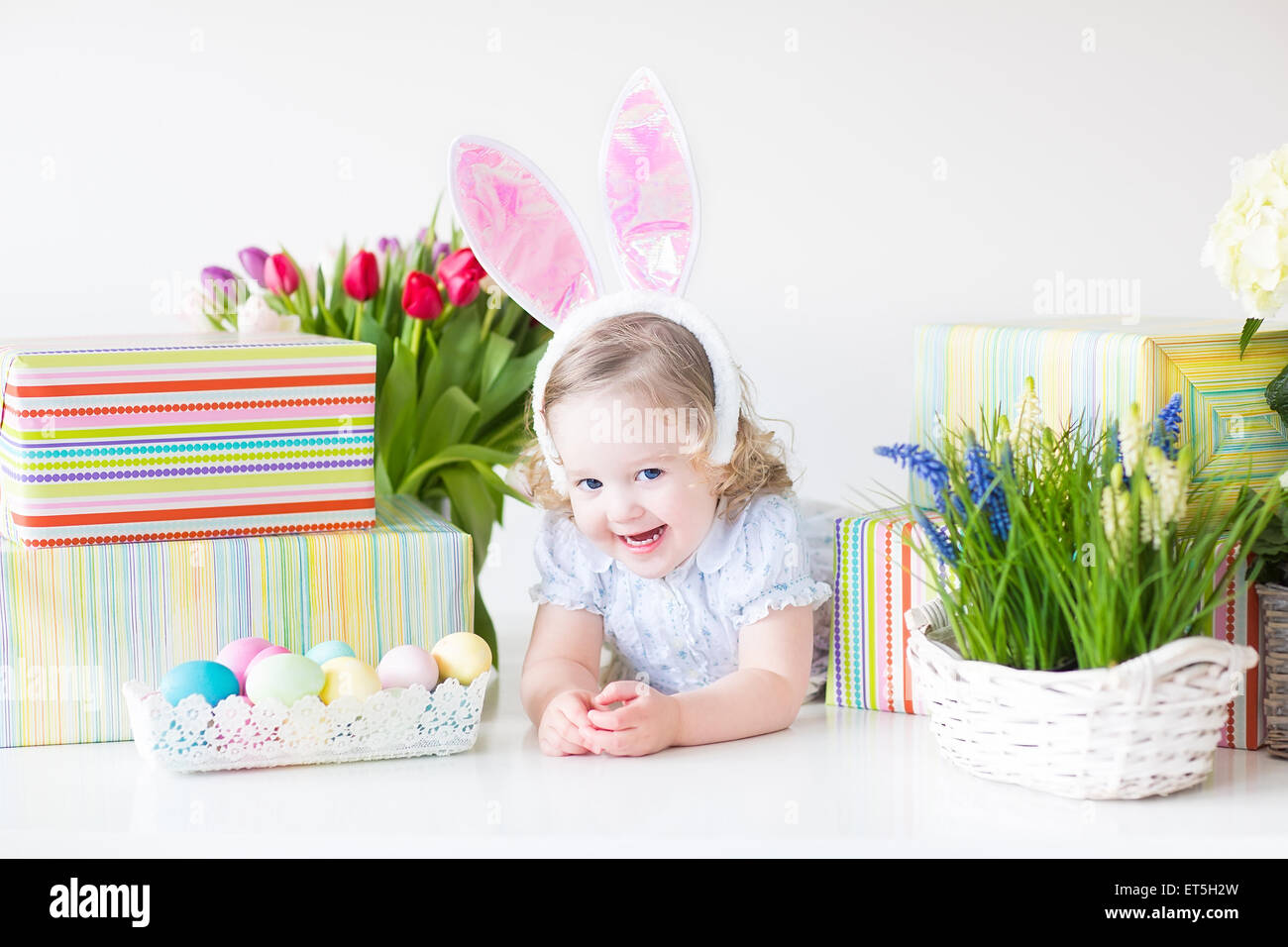 Happy laughing toddler girl wearing a blue dress and bunny ears happy laughing toddler girl wearing a blue dress and bunny ears playing with easter presents negle Gallery