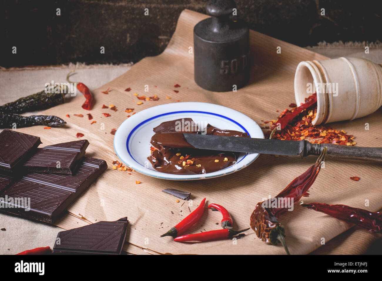 Chopping dark chocolate with fresh and dry red hot chili peppers ...