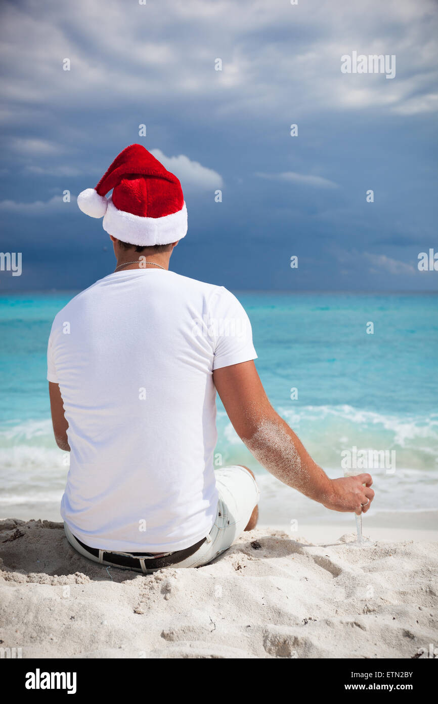 Single man in Santa Helper hat celebrating Christmas on beach with ...
