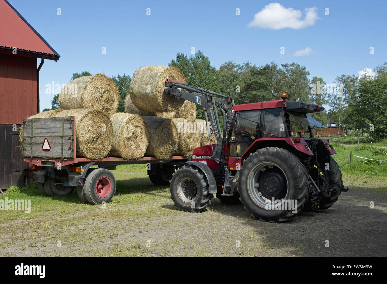 Hay Tractor With Loader : Loading round bale of hay into hayloft with front loader