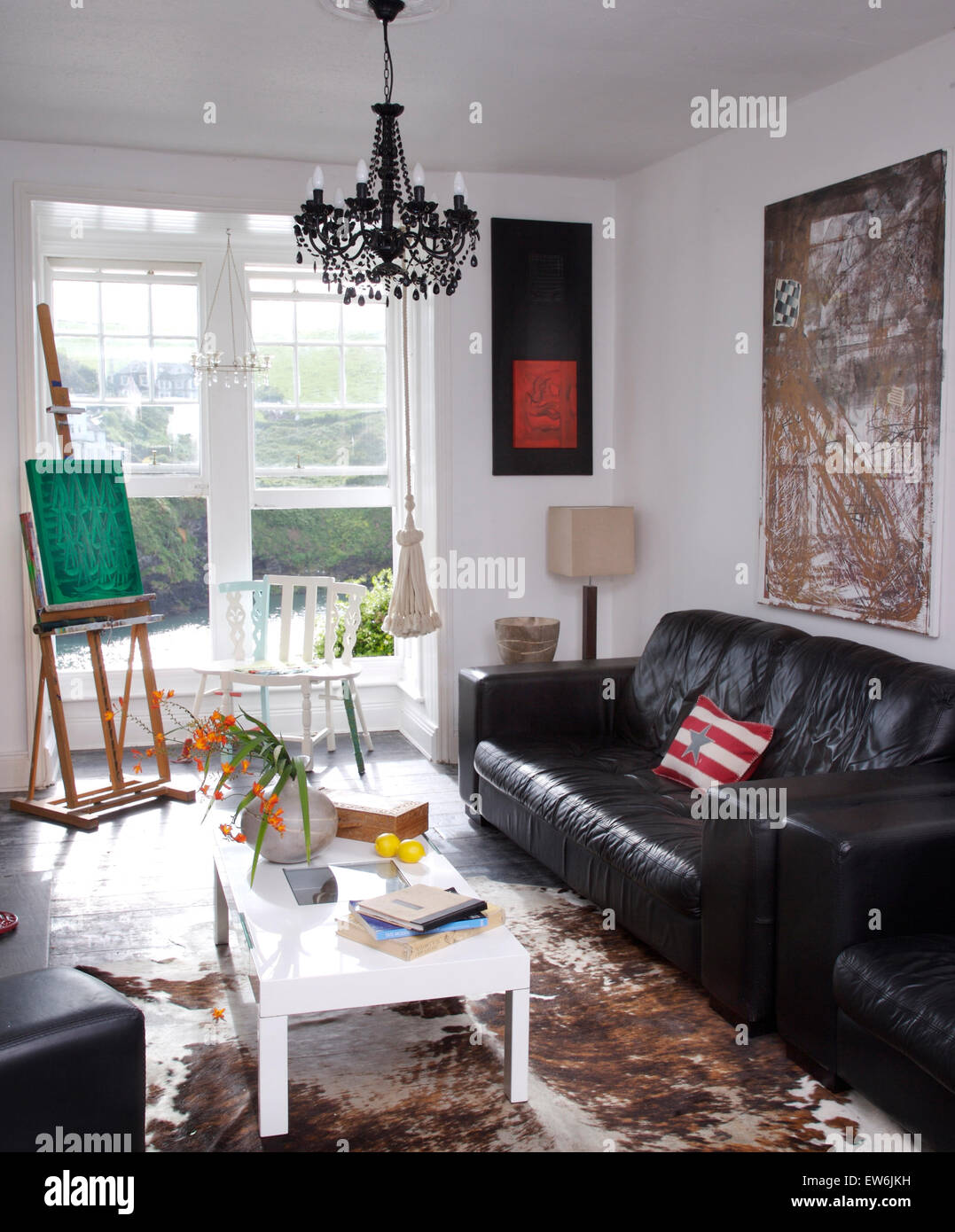 Black Leather Sofa And A White Coffee Table In Artist's
