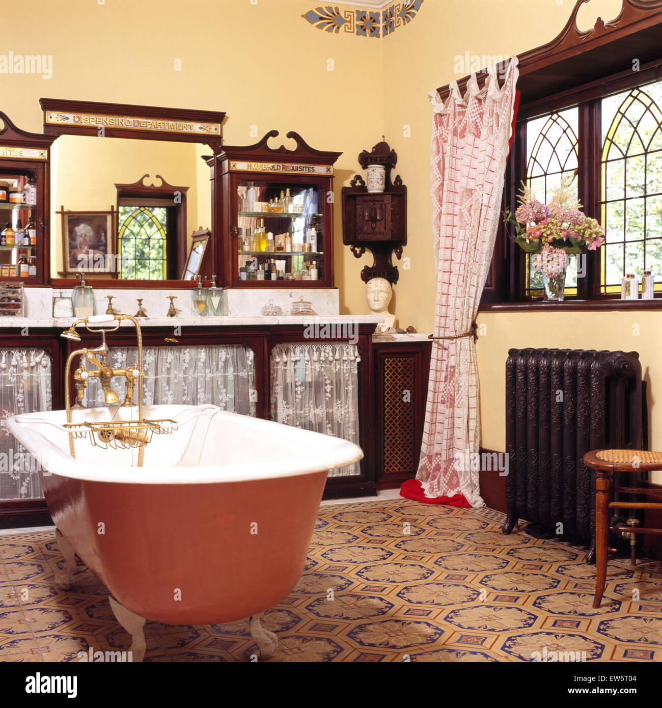 Painted roll top bath in nineties edwardian style bathroom with painted roll top bath in nineties edwardian style bathroom with patterned floor tiles and mahogany vanity unit dailygadgetfo Choice Image