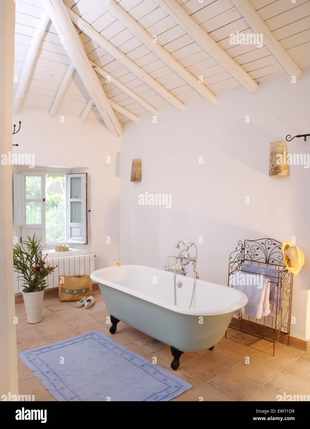 Roll top bath in white Spanish bathroom with white painted beamed ...