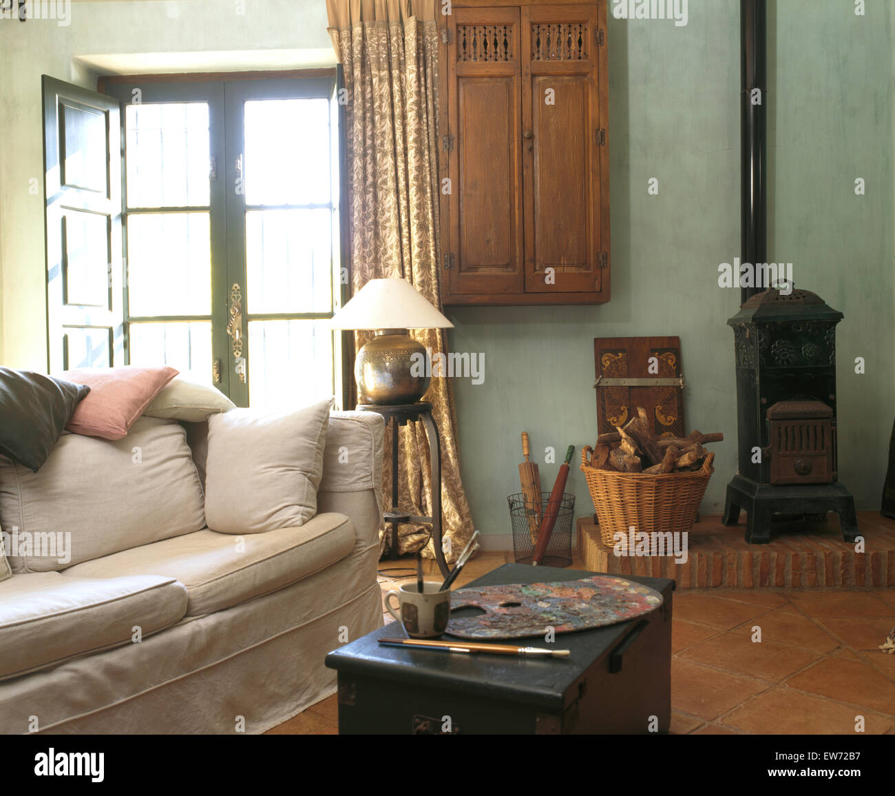 Small wood burning stove and white sofa in spanish country for Small room in spanish