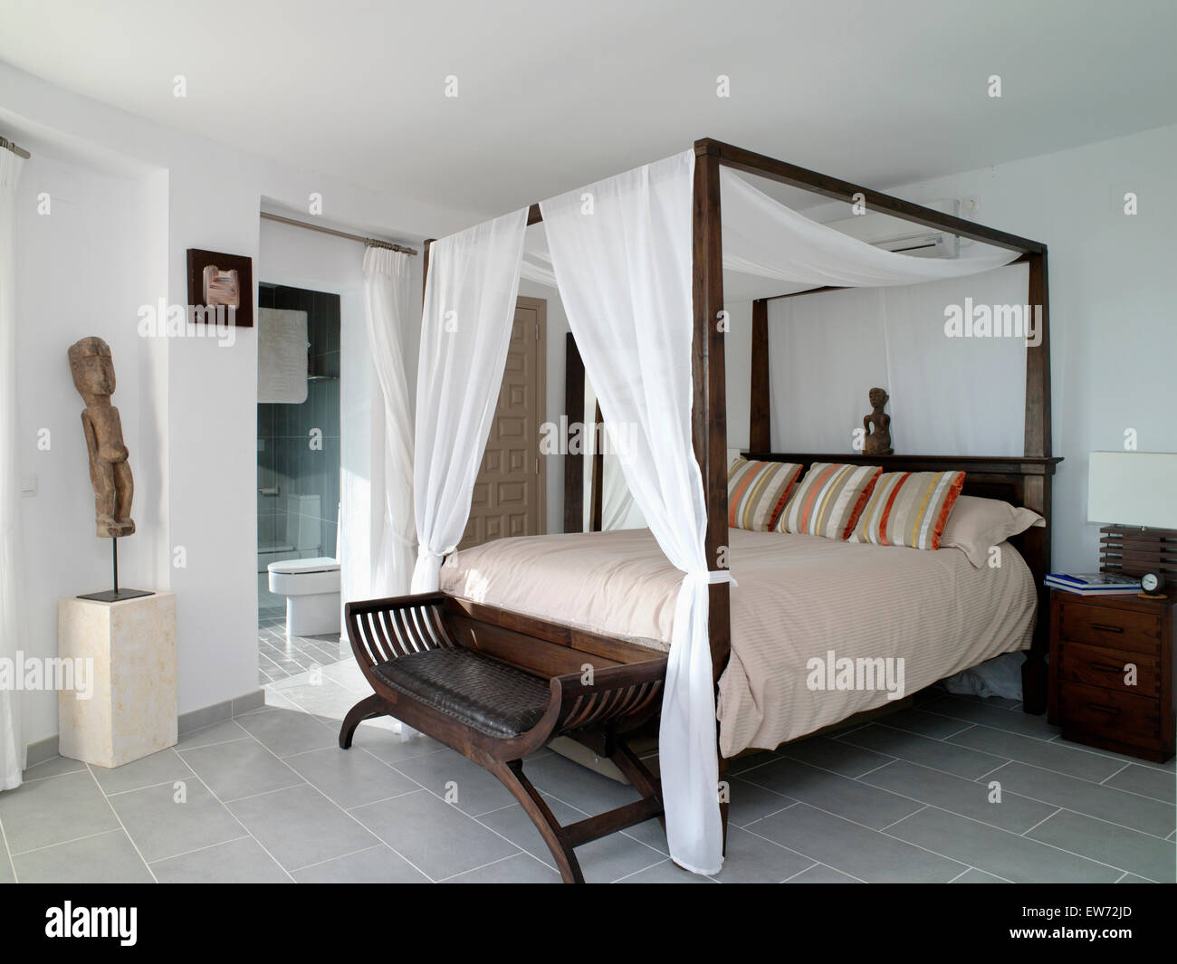 White drapes on simple four-poster bed in white coastal bedroom with ethnic sculpture on plinth & White drapes on simple four-poster bed in white coastal bedroom ...