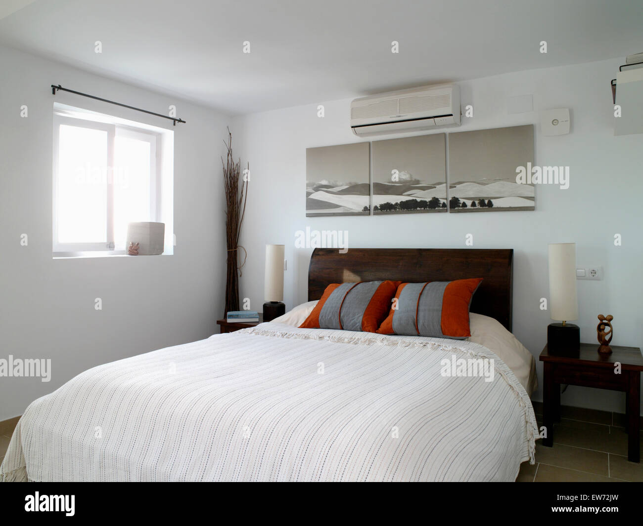 Air conditioning unit and large picture above bed with gray red cushions  and cream cover in modern bedroom. Air conditioning unit and large picture above bed with gray red