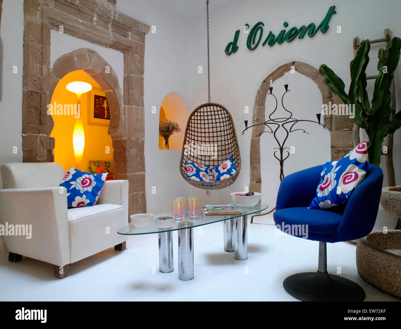Stock photo white and blue armchairs in modern moroccan living room with glass table and hanging chair beside arch with lighted lamp