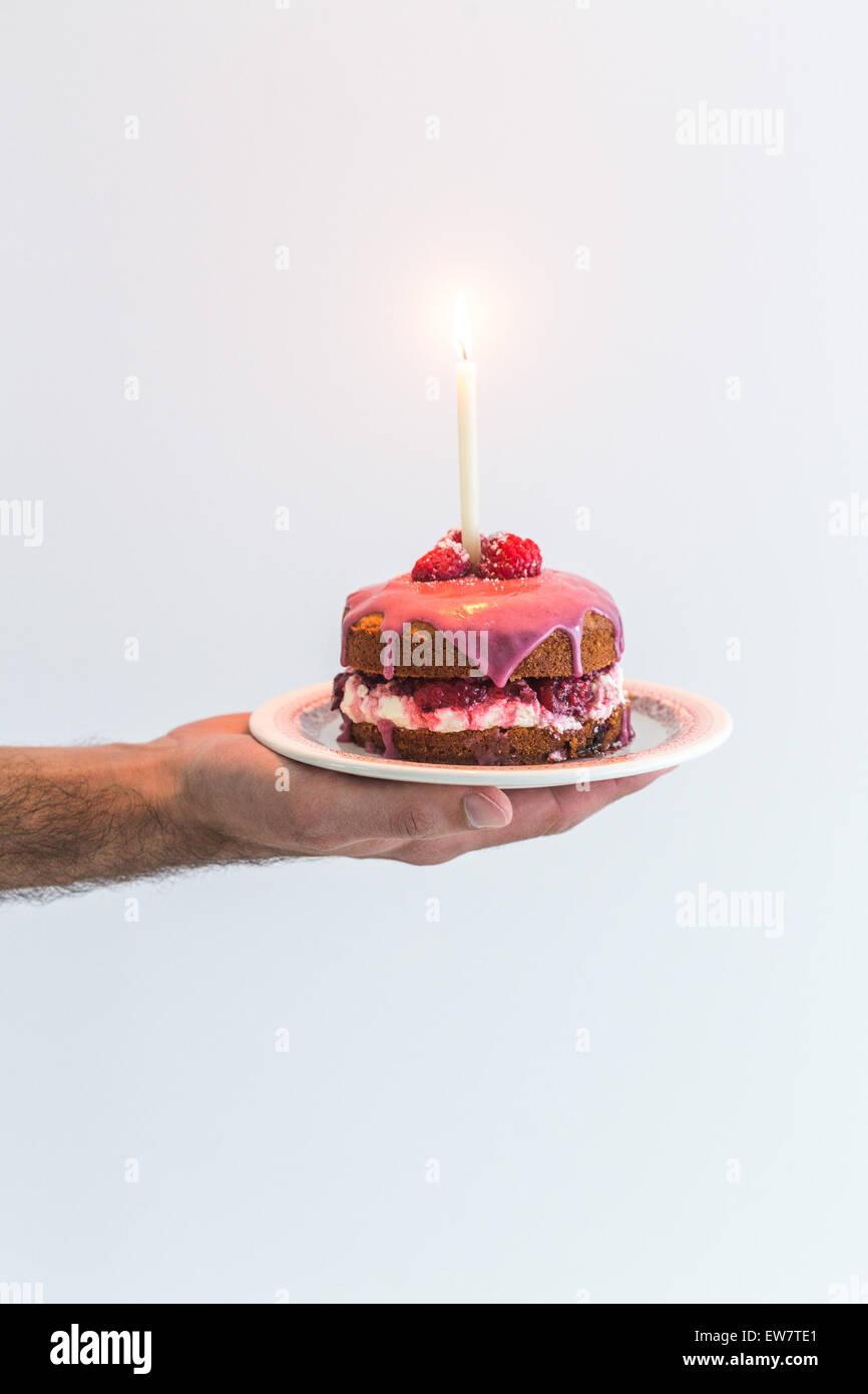 Mans hand holding a victoria sponge birthday cake with a candle mans hand holding a victoria sponge birthday cake with a candle sciox Image collections