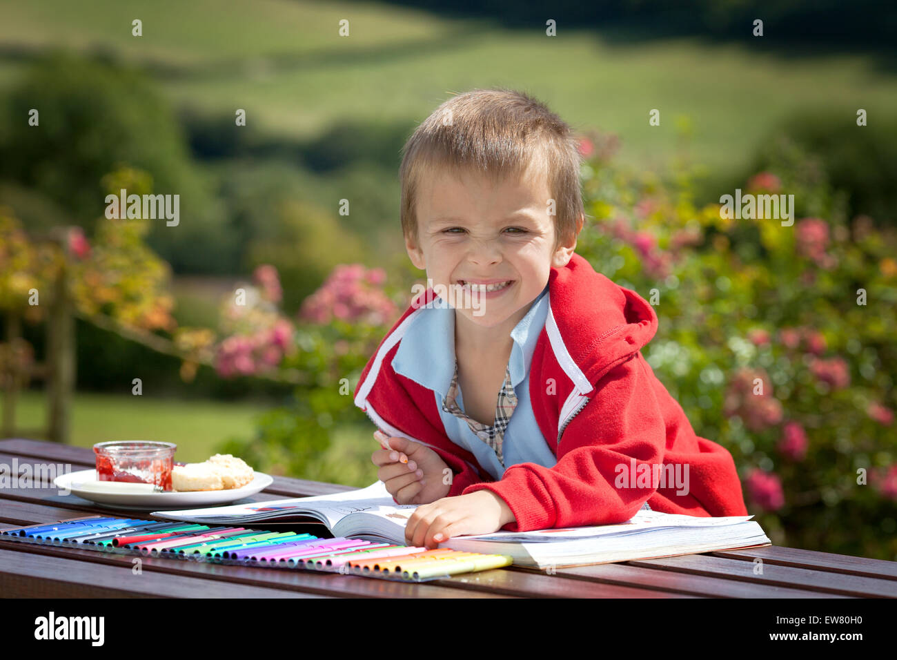 Adorable boy in red sweater, drawing a painting in a book, outdoor ...