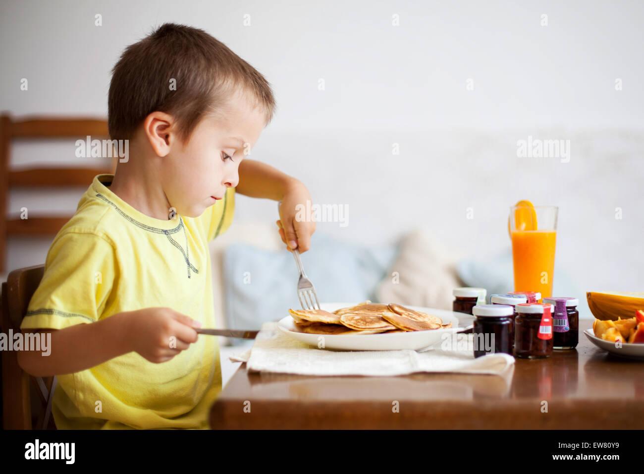 Cute boy, eating pancakes at home Stock Photo, Royalty ...
