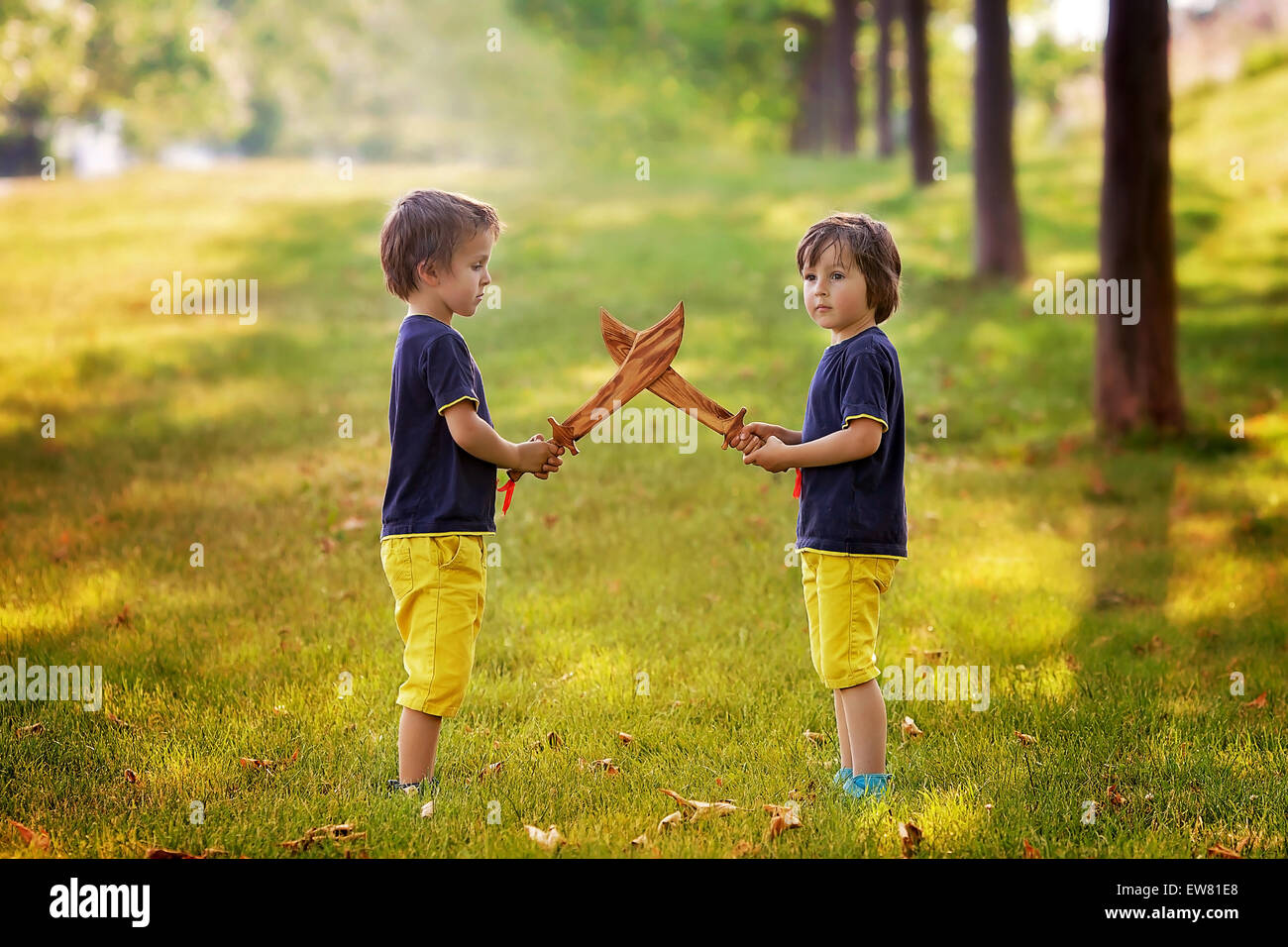 Two Little Boys Holding Swords Glaring With A Mad Face At Each Other Fighting Outdoors In The Park