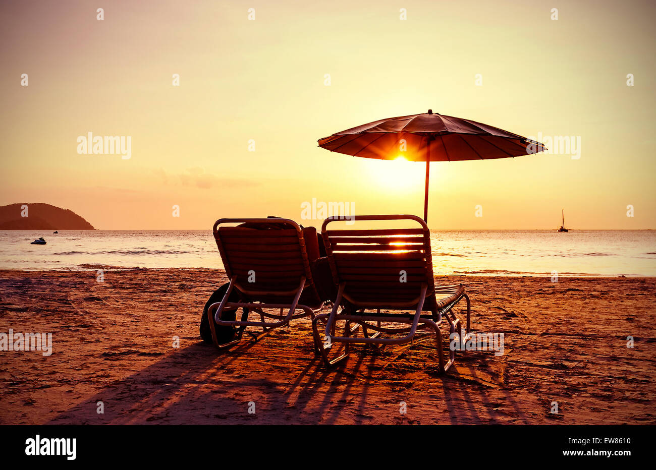Vintage instagram stylized beach chairs and umbrella at sunset Stock