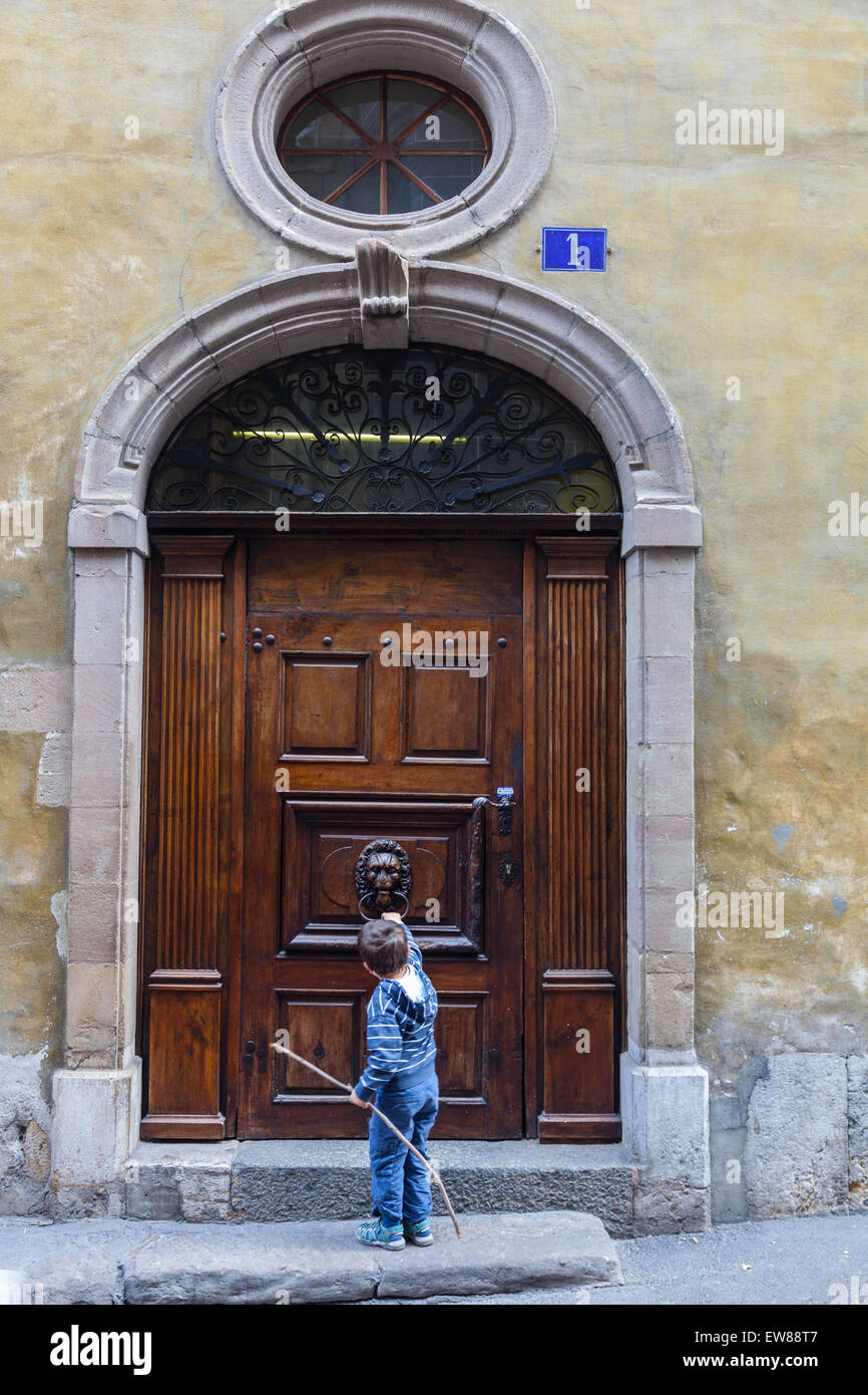 Young boy knocking on a large door in the old town of Geneva Switzerland & Young boy knocking on a large door in the old town of Geneva Stock ...