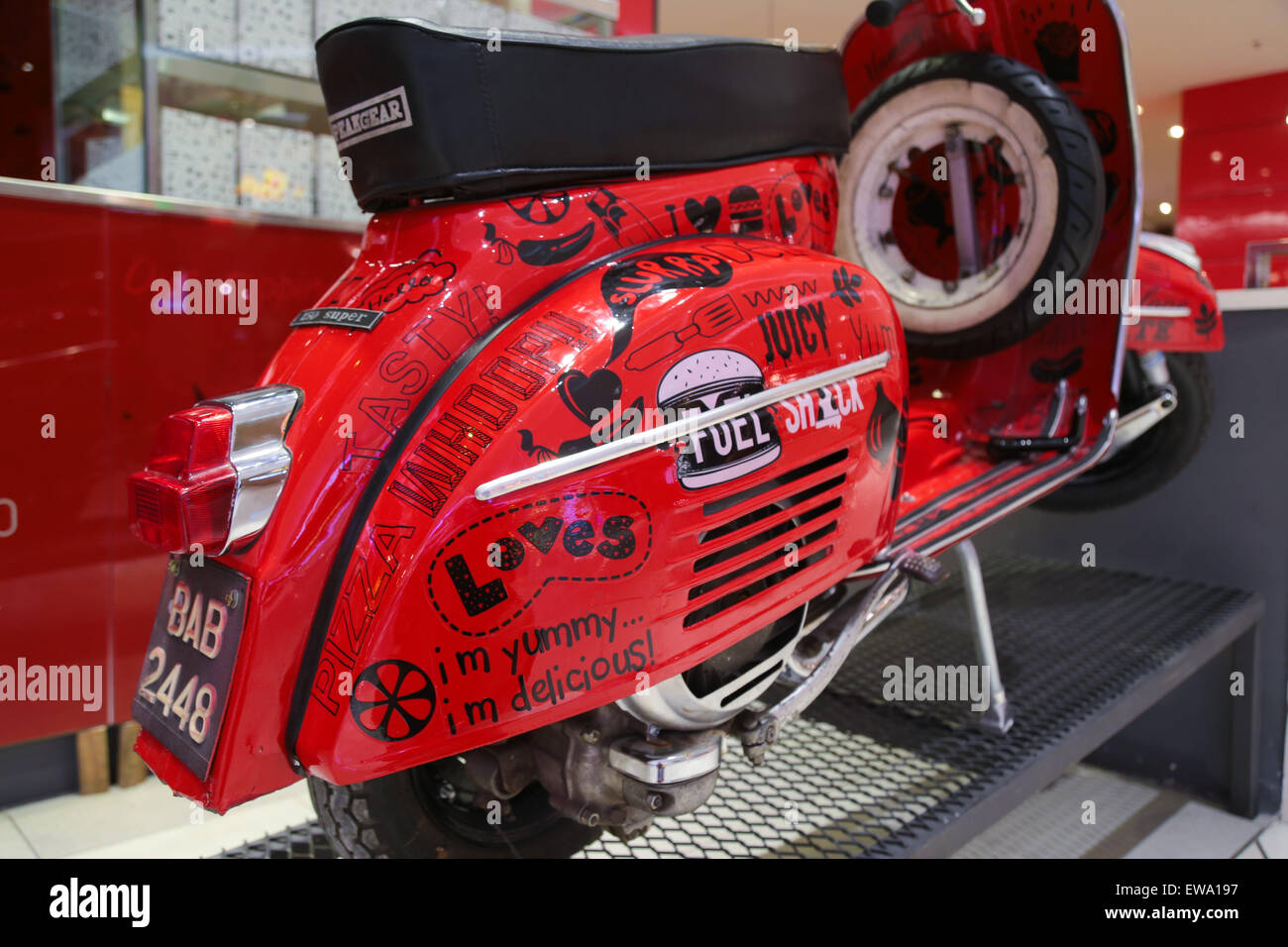 A classic piaggio vespa painted red with appertising words for Vespa decoration