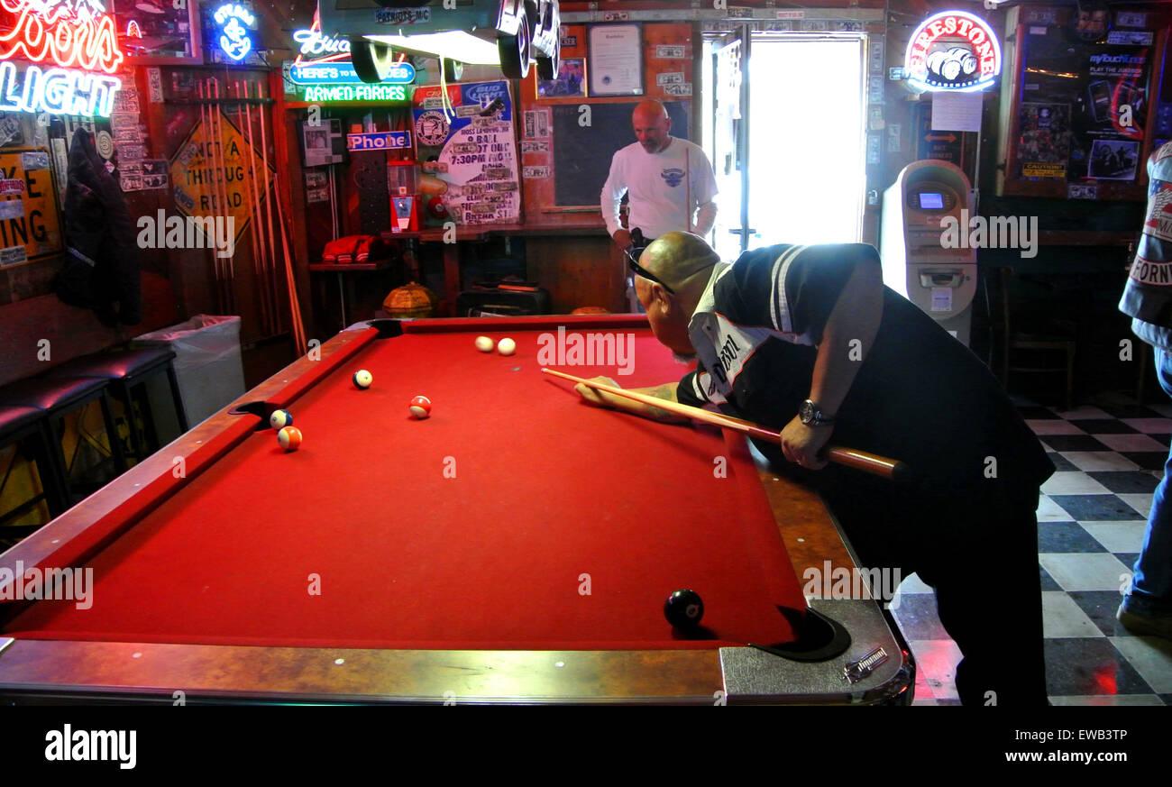 black man white man play pool on red velvet pool table in biker