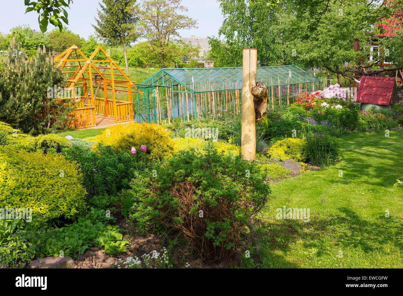 Summer fine European garden landscape. Decorative bushes trees and ...