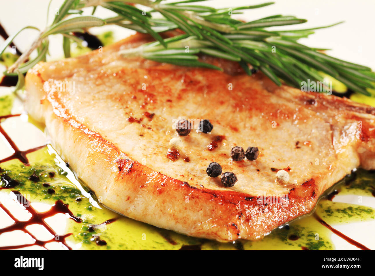 Pan Fried Pork Chop Decorated With Pesto Sauce And Balsamic Drizzle