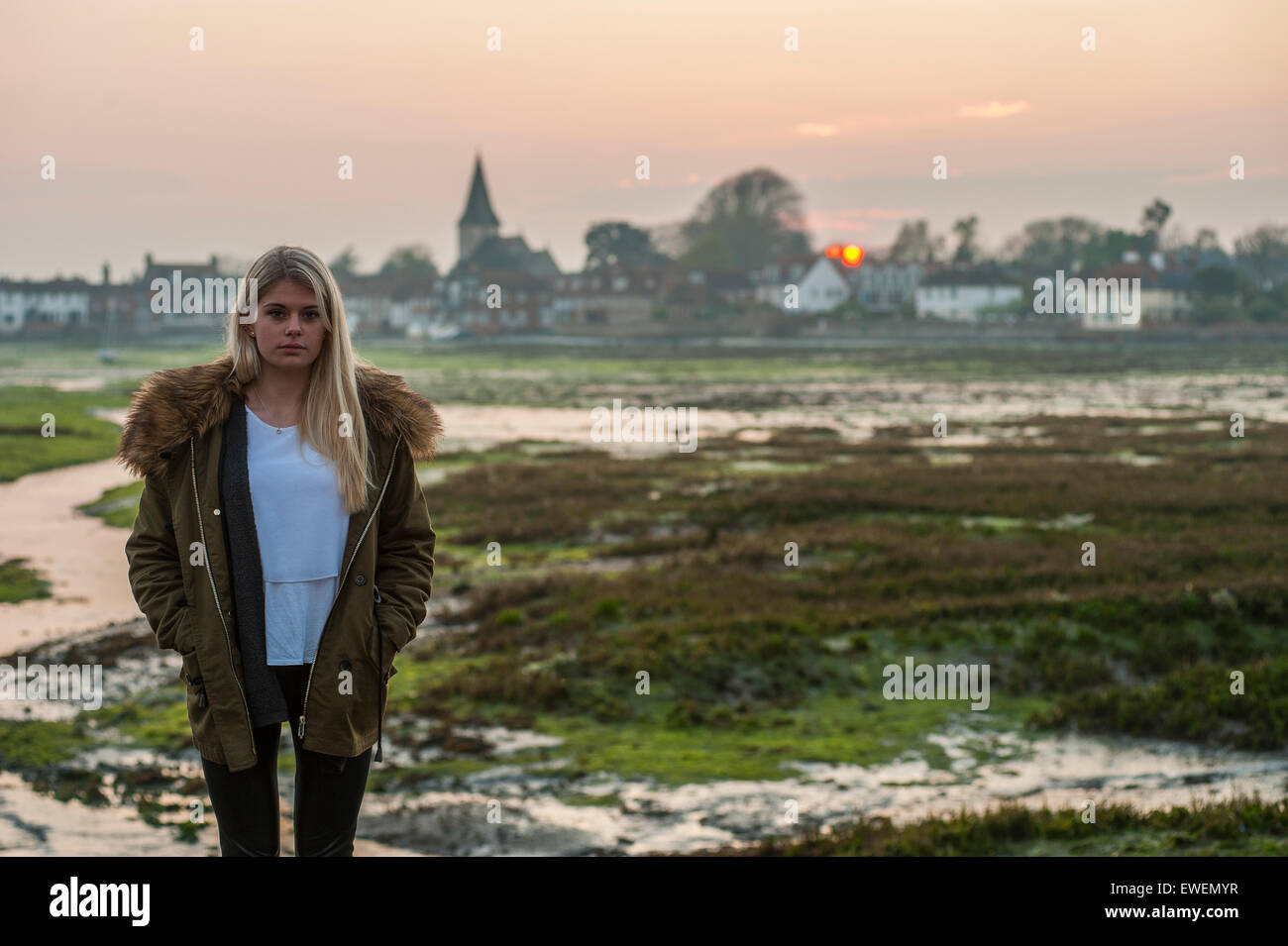 a pretty girl stands in front of a sunset over a quintessential a pretty girl stands in front of a sunset over a quintessential english village
