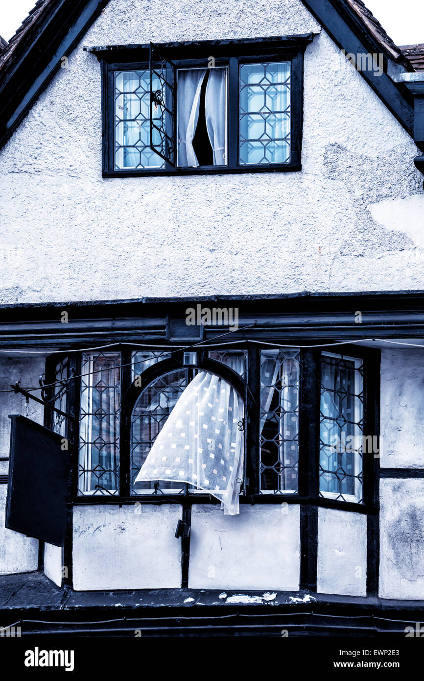 Open window with curtains blowing -  Old House In Tudor Style With A Curtain Blowing Out Of A Window Stock Photo
