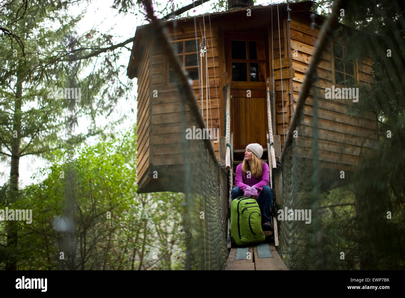 Hanging Tree House Adult Woman With Her Backpack Hanging Out In Front Of A Tree House