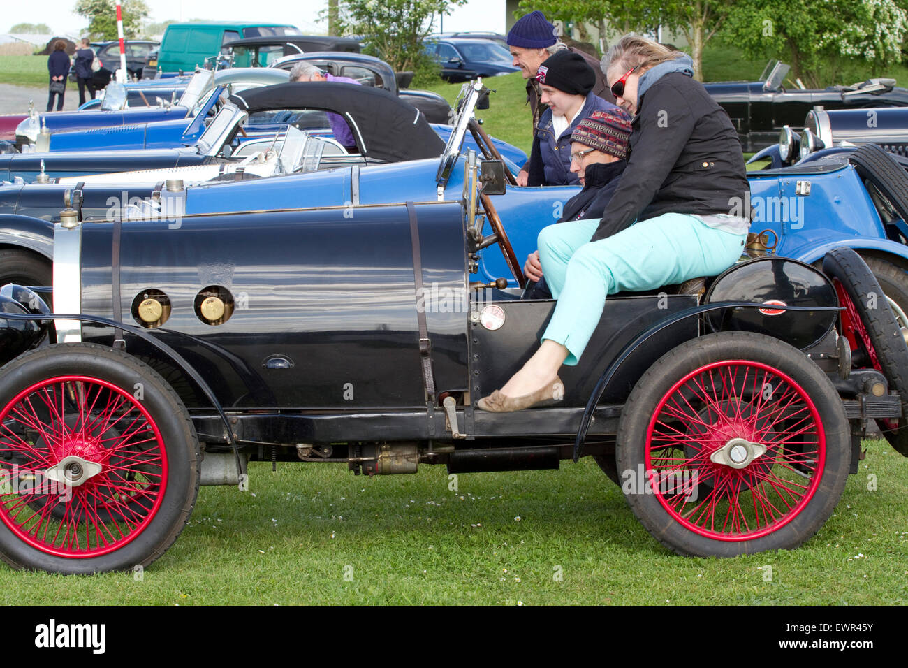 Women getting out of an open top vintage Bugatti at an outdoor ...